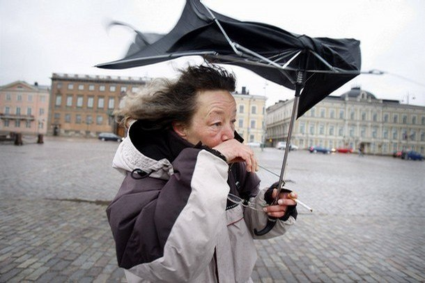 A woman tries to smoke under her broken umbrella at market place in Helsinki