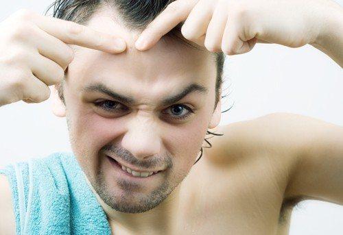 Man picking pimple.