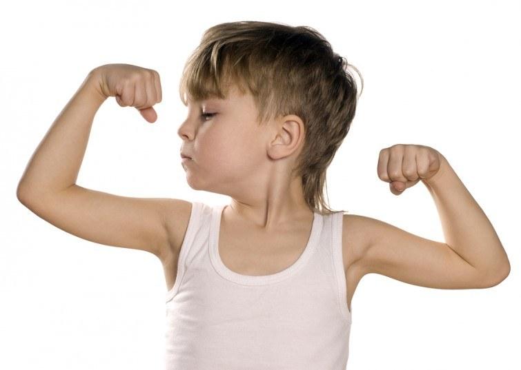 Portrait of little european boy flexing biceps. Beautiful caucas