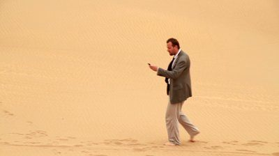 stock-footage-businessman-searching-for-signal-on-cellphone-in-the-desert