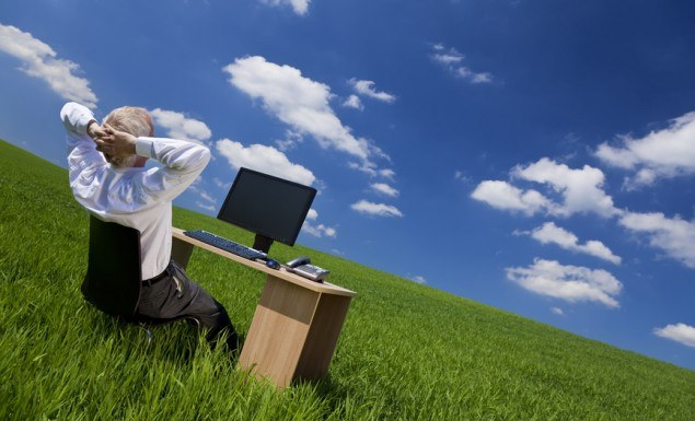 Business concept shot of a middle aged man or businessman relaxing with hands behind his head at an office desk with computer in a green field with a bright blu