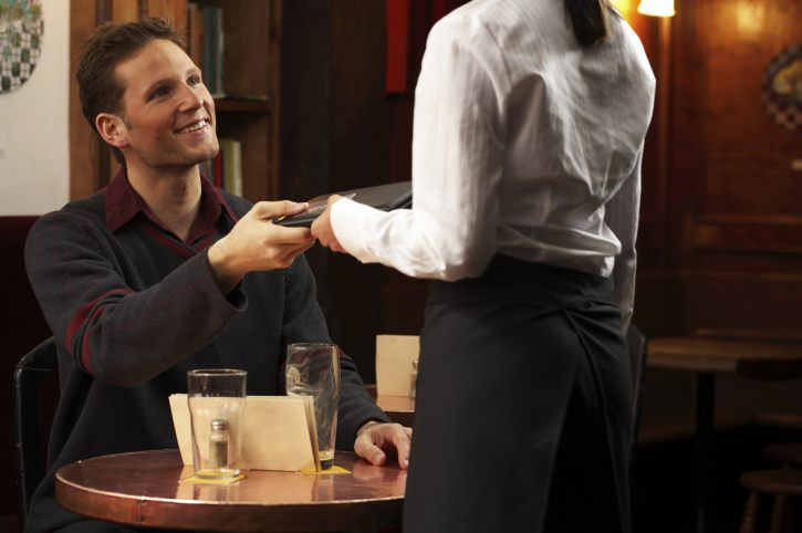 Man in restaurant paying waitress