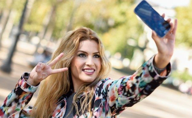 young-woman-taking-selfie-and-showing-victory-gesture_1139-409