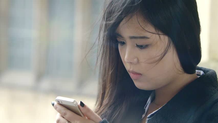 Shutterstock, https://www.shutterstock.com/video/clip-13340354-stock-footage-worried-and-sad-asian-woman-typing-a-short-message-on-the-mobile-phone.html