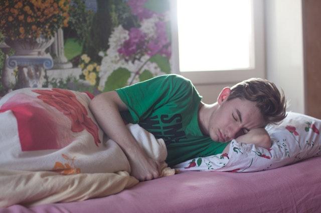 Pexels, https://www.pexels.com/photo/man-wearing-green-printed-crew-neck-shirt-while-sleeping-296817/